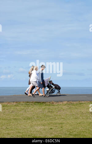 Family with young child in pushchair on coastal path in Blackpool, Lancashire - Stock Photo