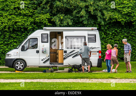 A motorhome couple with their dog, chat to another couple on a Caravan Club campsite pitch in England, UK. - Stock Photo