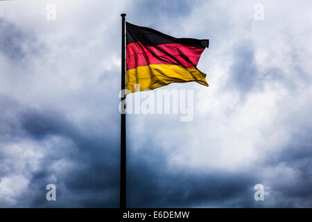 Storm clouds gathering behind the German flag, symbolic of political crisis, war or unrest. - Stock Photo
