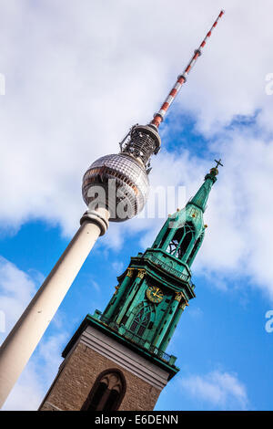 The Fernsehturm or Television Tower and the Marienkirche in Berlin, a juxtaposition of religion and science. - Stock Photo