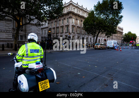 Police motorcyclist of the Metropolitan Police in London stands ready in Whitehall at the junction with Downing - Stock Photo