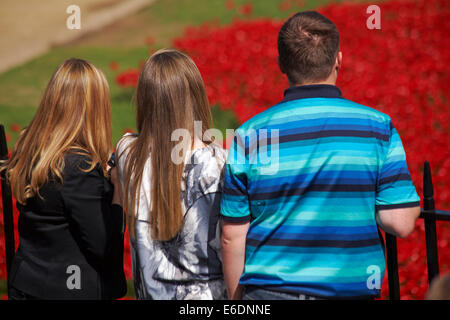 family looking at ceramic poppies of Blood Swept Lands and Seas of Red at Tower of London to mark centenary of WW1 - Stock Photo