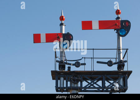 Vintage British train signal in the stop position on the West Somerset Railway, against clear blue sky. - Stock Photo