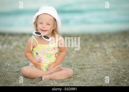 Little girl with Down syndrome playing sunglasses on the beach - Stock Photo