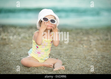 little girl with Down syndrome wore glasses and poses faces - Stock Photo