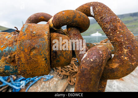 Rusty anchor chain knot and the yacht Vive La Vie owned by Willy Michel, founder of Ypsomed. - Stock Photo