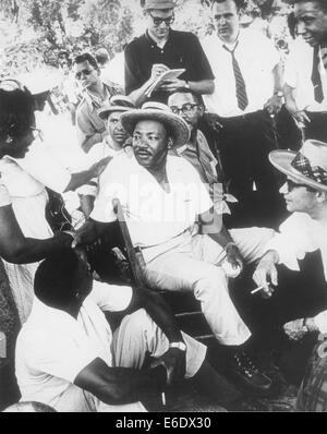 Martin Luther King, Jr in Straw Hat Sitting Down with Group of Men While Shaking Hands with Woman, circa 1960's - Stock Photo