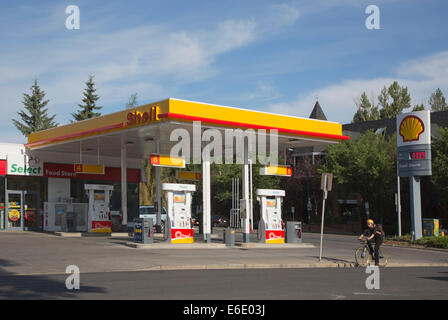 Cyclist riding past Shell service station with sign showing the price per litre in Canadian dollars - Stock Photo