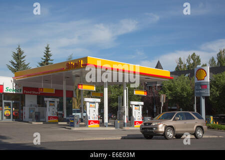 SUV driving past Shell service station with sign showing the price per litre in Canadian dollars - Stock Photo