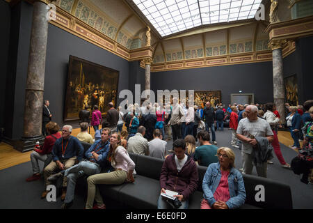 People watching 'the Nachtwacht' and other famous paintings by Rembrandt van Rijn at the Rijksmuseum in Amsterdam. - Stock Photo