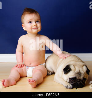 9 month old baby sitting with his pug dog. - Stock Photo