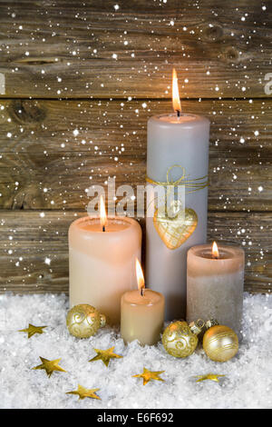 Festive christmas decoration in gold and white: four red burning advent candles on wooden background. - Stock Photo