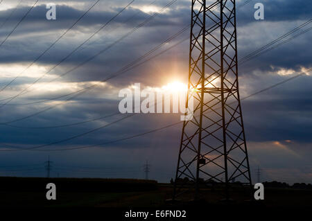 Markgroeningen, Germany. 22nd Aug, 2014. The sun shines through dark clouds in a morning sky behind a high-tension - Stock Photo