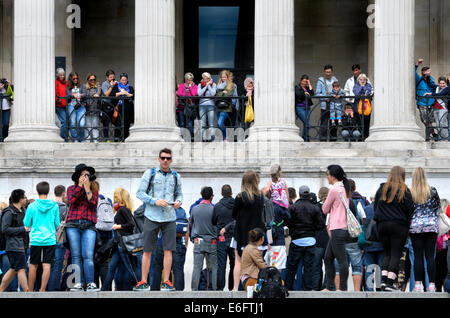 London, England, UK. People on the steps in Trafalgar Square and in the entrance to the National Gallery - Stock Photo