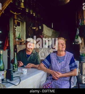 Couple of elderly mountain farmers sitting in front of their chalet Savoy French Alps France - Stock Photo