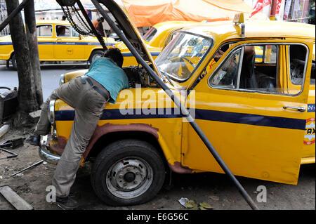 INDIA West Bengal, Kolkata, open garage in Elgin Road , open air repair of a HM Ambassador yellow cab, the car is - Stock Photo