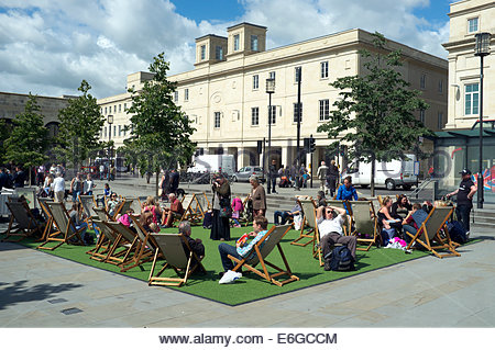 People relax on deckchairs and artificial grass, at Bath's Brunel Square Piazza. SouthGate shopping centre visible - Stock Photo