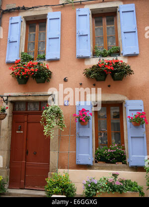 Blue shutters and flower baskets outside a French house in Mirepoix France - Stock Photo