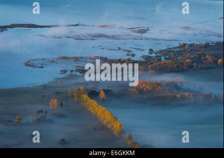 Areal photo of foggy Cerknica lake in dawn. - Stock Photo