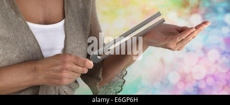 Female Sound Healer using a tuning fork against palm of hand with pastel colored bokeh background - Stock Photo
