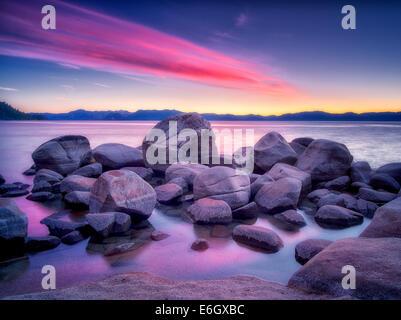 Boulder rocks and sunset on shoreline of Chimney Beach. Lake Tahoe, Nevada - Stock Photo