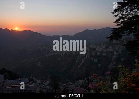 The evening sun setting behind the Himalayan foothills in Shimla, Himachal Pradesh, India, - Stock Photo
