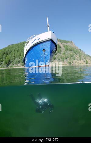 Split level, diver swims under the boat, lake Baikal, Siberia, Russia, Eurasia - Stock Photo