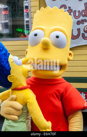 Bart Simpson television character holding sister Maggie Simpson at Universal Studios in Orlando Florida - Stock Photo