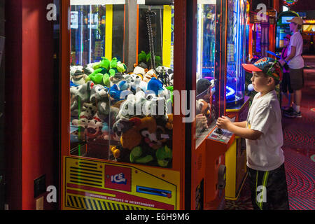 Young boy playing skill game to win stuffed animal in the arcade inside the Contemporary Resort in Walt Disney World, - Stock Photo