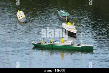 Model ships on lake enacting naval warfare.