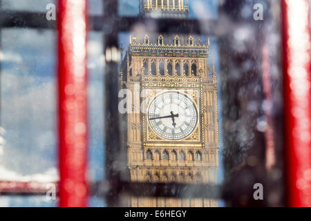 Big Ben Clock Tower of the Houses of Parliament seen through windows of traditional red telephone box London England - Stock Photo