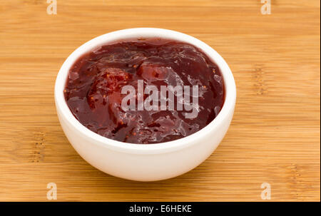 Small pot of strawberry Jam on a wooden board - Stock Photo