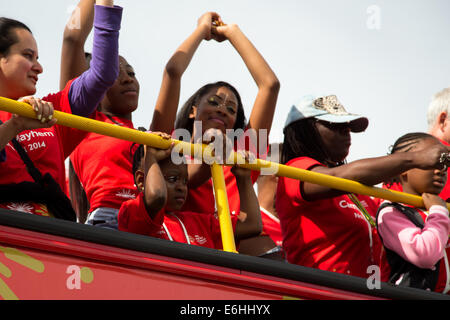 A young girl lost in thought among revelers during the  2014 Notting Hill Carnival parade - Stock Photo
