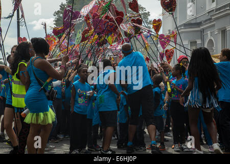 London, UK. 24th Aug, 2014. Revellers in blue t-shirts carrying hearts parade at 2014 Notting HIll Carnival, children's - Stock Photo