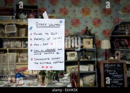 A hand written sign notice in a shop window advertising jobs staff vacancies. - Stock Photo