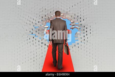 Businessman walking on arrow pierced brick wall - Stock Photo