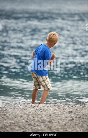Rear view of a child blond boy skimming pebbles into the sea summertime - Stock Photo