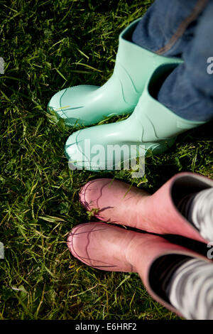 'Point of view' of children wearing wellington boots on grass. - Stock Photo