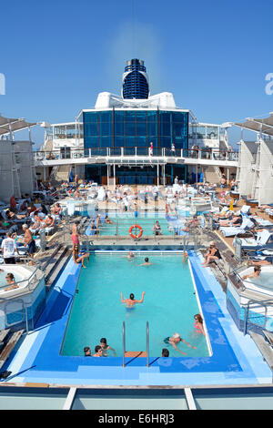 People in cruise ship liner swimming pools and Jacuzzi relaxing on the sunbathing deck cruising the Mediterranean - Stock Photo