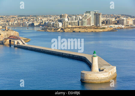 Green channel light on end of Grand Harbour wall with Saint Elmo Bridge and modern high rise building development - Stock Photo