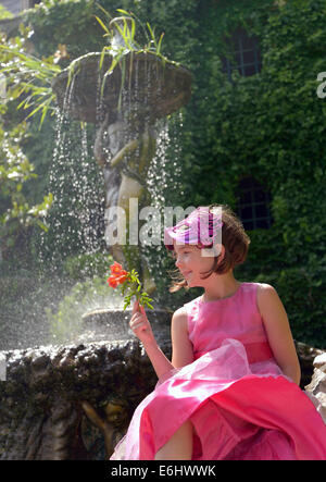 Outdoor portrait of pretty young girl in pink party dress wearing mask and holding flower. - Stock Photo