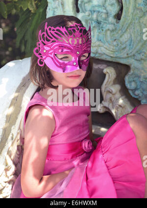 Portrait of pretty young girl in pink dress wearing party mask outside. - Stock Photo