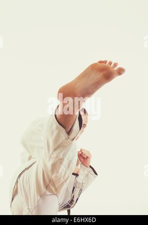 Man fighter in kimono beat a high leg kick, High kick with a leg - Stock Photo