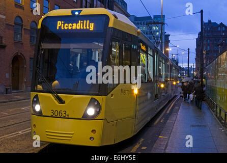 Yellow Manchester trams at dusk, England, UK - Stock Photo
