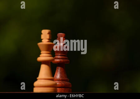 Two chess  Kings facing each other in dark green background. - Stock Photo