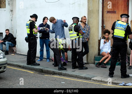London, UK. 24th August, 2014. Notting Hill Carnival 2014. Police carry out stop and search on young Carnival goers - Stock Photo