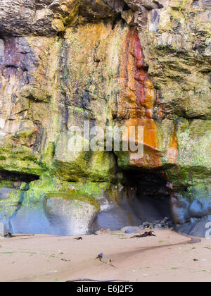 Wave worn cliffs in former iron mining area with a small mined adit entrance and iron staining Saltburn Cleveland - Stock Photo