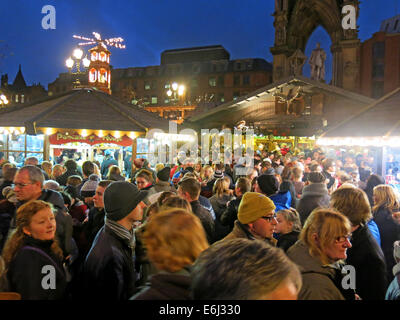 Visitors & shoppers enjoying Manchester Christmas German Markets in Albert Square , December at dusk - Stock Photo
