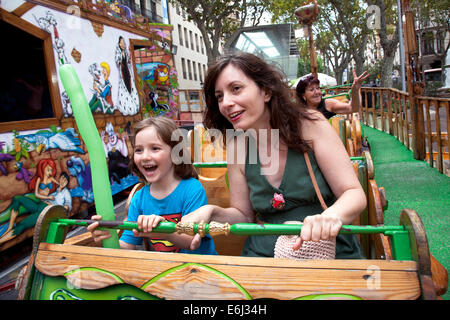 Mother and young son on fairground ride, Barcelona, Spain. - Stock Photo