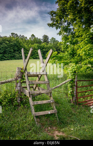 A wooden stile helps hikers  traverse a barbed wire fence guarding farmland along the Appalachian Trail - Stock Photo